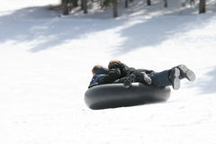 Children sledding. Or tubing down a snowy hill in northern wyoming Royalty Free Stock Photos