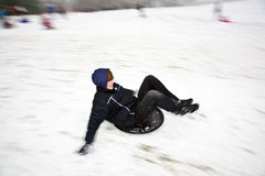 Children are sledding down the hill in snow Stock Photography
