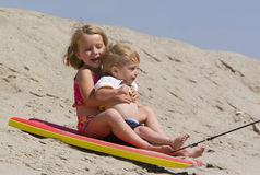 Children sledding down sand dune. Two children, a girl and boy laughing while sledding on a boogy board down a sand dune at the beach royalty free stock photo