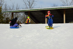 Children Sledding At Millenium Park. Three children sledding at Millenium Park in Twin Lakes, Wisconsin in Kenosha County in the United States of America royalty free stock images
