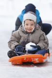 Children sledding on the snow. Older brother pushig a sled with his younger sibling down the icy hill Stock Photo