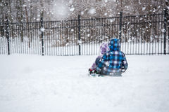 Children Sledding in Winter Snowfall Royalty Free Stock Photo
