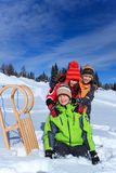 Children with sledge in Winter. Three happy children on snow mountainside with sledge in Winter stock photo