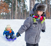 Children on sleds in snow Stock Photo
