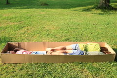 Children sleeping in a box. Barefoot children - two boys and girl lying and sleeping in a paper box Stock Image