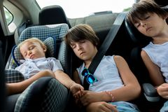 Children, sleeping in carseats while traveling. Tired children, sleeping in carseats while traveling, holding hands to sooth royalty free stock photography