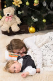Children sleeping at christmas tree. Girl and her younger brother sleeping at christmas tree indoors Royalty Free Stock Image