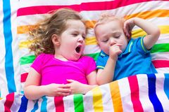 Children sleeping under colorful blanket. Two kids sleeping in bed under colorful blanket. Children relaxing in bedroom. Tired toddler girl and baby boy before Royalty Free Stock Images