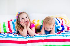Children sleeping under colorful blanket Stock Images