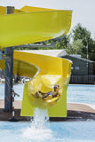 Children slide down a water slide Royalty Free Stock Photo