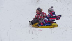 Children slides from the mountain in the snow. Winter, leisure, sport, and people concept - happy teenage boy or young man sliding down on snow tube over stock video footage