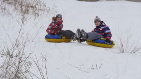 Children slides from the mountain in the snow stock footage