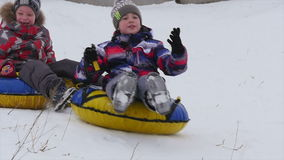 Children slides from the mountain in the snow stock video
