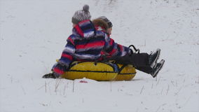 Children slides from the mountain in the snow. Winter, leisure, sport, and people concept - happy teenage boy or young man sliding down on snow tube over stock video