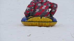 Children slides from the mountain in the snow. Winter, leisure, sport, and people concept - happy teenage boy or young man sliding down on snow tube over stock footage