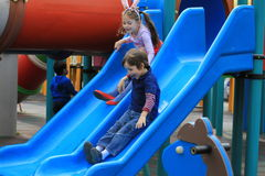 Children sliding. Brother and sister playing in park on a slide Stock Photography