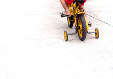 Children with slippers cycling bike with training wheels Royalty Free Stock Image