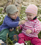 Children smelling the flowers. Boy letting his little sweetheart smell the flower he picked for her Royalty Free Stock Photo