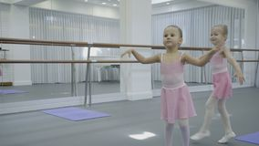Children smile and dance in training against backdrop of ballet machines. Little girls smoothly move their hands during classes near large mirrors stock video