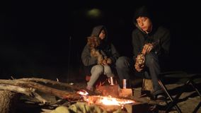Children smile kids drink tea teen sit by the fire lifestyle at night campfire. travel hiking adventure camping. Children smile kids drink tea teen sit by fire stock video footage