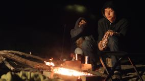 Children smile kids drink tea teen sit by the fire at night campfire lifestyle. travel hiking adventure camping. Children smile kids drink tea teen sit by fire stock footage