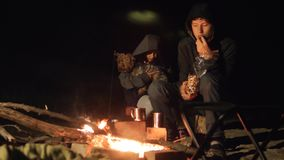 Children smile kids drink tea teen sit by the fire at night campfire. lifestyle travel hiking adventure camping. Children smile kids drink tea teen sit by fire stock video footage