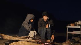 Children smile kids drink tea teen sit by the fire at night campfire. travel hiking adventure camping adventure camping. Children smile kids drink tea teen sit stock footage