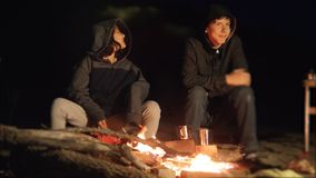 Children smile kids drink tea teen sit by the fire at night campfire. travel hiking adventure camping adventure. Children smile kids drink tea teen sit by fire stock footage