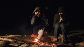 Children smile kids drink tea teen sit by the fire at night campfire. travel hiking adventure camping adventure camping. Tourists are warming themselves by stock footage