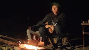 Children smile kids drink tea teen sit by the fire at night campfire. travel lifestyle hiking adventure camping. Children smile kids drink tea teen sit by fire stock video footage