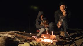 Children smile kids drink tea teen sit by the fire at night lifestyle campfire. travel hiking adventure camping. Children smile kids drink tea teen sit by fire stock video