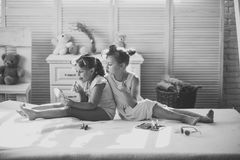 Children smile and sit on bed with lipstick, nail polish and mirror Stock Image
