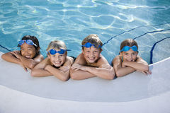 Children smiling at edge of swimming pool Royalty Free Stock Photography