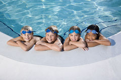 Children smiling at edge of swimming pool stock photography