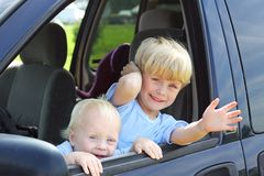 Children Smiling Out Van Window. Two cute brothers leaning out a van window, smiling and waving stock photos