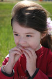 Children- Snack Time. Little girl eating a snack outside on the playground Stock Photo