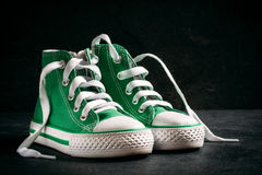 Children sneakers. Small green and urban style sneakers on dark background,selective focus Royalty Free Stock Photo