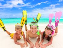 Children with snorkels by sea. Three happy young children with colorful snorkels and flippers on sandy tropical beach, sea and cloudscape background Stock Photo