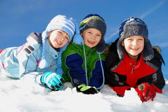 Children in snow. Three happy smiling caucasian white kids in winter clothes lying in the snow and staring Royalty Free Stock Images