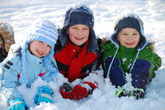 Children in snow. Sister with brothers in winter clothes outdoors laying on snow Royalty Free Stock Photography