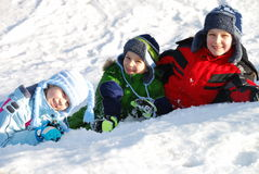 Children in snow. Three caucasian white kids in warm winter clothes smiling and lying in the snow Stock Photo