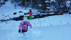 Children in snow by creek Royalty Free Stock Image