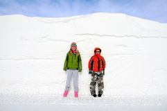 Children and Snow Drift. Two Children Measure Up Against Tall Snowdrift Stock Images