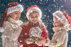 Children with snow globe. Merry Christmas and happy holidays! Cute little children with snow globe. Kids enjoying the holiday on dark background royalty free stock photo