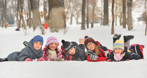 Children in the snow in winter. Group of children playing on snow in winter time stock image