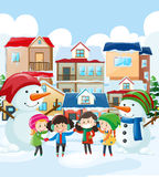 Children and snowman in the village Stock Photos