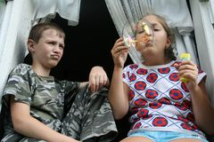 Children and soap-bubble. Boy and girl sitting on the window and blow bubbles stock image
