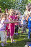 Children and soap bubbles. Happy children playing with soap bubbles on May 30, 2015 in Bucharest, Romania royalty free stock photography