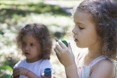 Children and soap bubbles. Little girls blowing soap bubbles stock images
