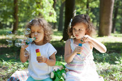 Children and soap bubbles. Little girls blowing soap bubbles royalty free stock photo